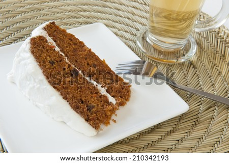 Slice of carrot cake with white icing and a cup of tea - stock photo