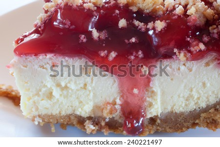 Slice of cheescake with cherry topping running down the side - stock photo