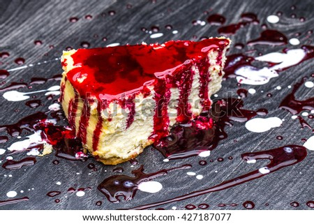 Slice of cheesecake topped with cherry compote on plate on brown table with dessert fork, top view - stock photo