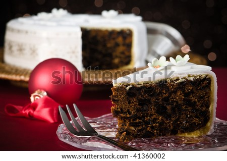 Slice of Christmas cake with dessert fork, remainder of cake  in festive background - stock photo