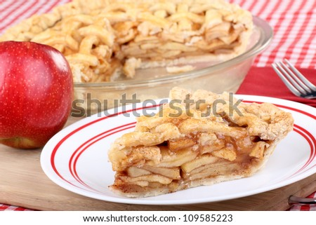 Slice of cinnamon apple pie and an apple - stock photo