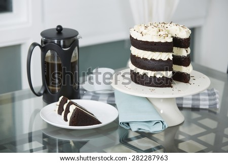 Slice of Decadent Chocolate Triple Layer Cake Served on Plate with Freshly Brewed Coffee in Bodum - stock photo