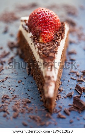 Slice of delicious chocolate and mascarpone cake with a fresh strawberry and roughly chopped chocolate flakes. Shallow DOF. - stock photo