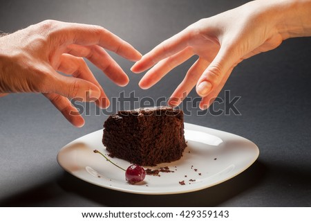 Slice of delicious chocolate cake with cherry on a white plate on a dark background. Male and female hand trying to grab a piece of cake. Greed for sweets concept with hand and chocolate cake. - stock photo