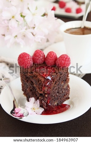 Slice of delicious chocolate cake with strawberry garnish and marmalade. Selective focus. - stock photo
