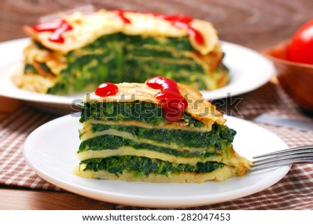 slice of delicious pancake cake filled with spinach and cheese - stock photo