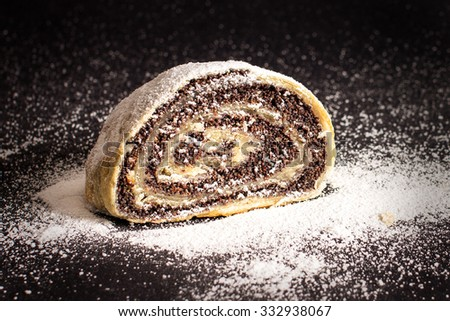 Slice of fresh baked homemade strudel with poppy seeds and sugar powder, isolated on a black background - stock photo