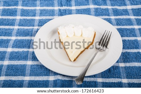 Slice of fresh lemon meringue pie on a white plate with fork on blue plaid placemat - stock photo