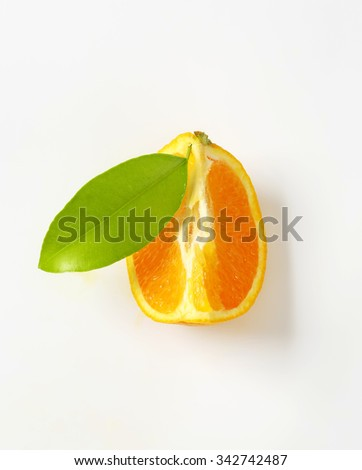 slice of fresh orange with leaf on white background - stock photo