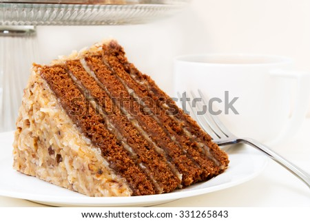 Slice of german chocolate cake closeup with cup of coffee.  Isolated on white background. - stock photo
