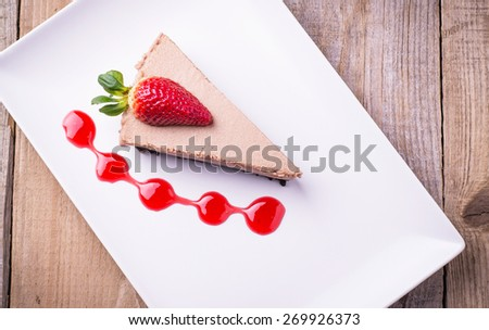 Slice of home made chocolate cheese cake with fresh strawberry and topping - stock photo