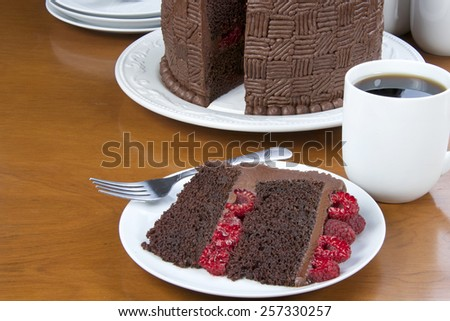 Slice of Home made original design chocolate cake with fresh raspberry filling and raspberries on top served on a plate with whole cake in the background. Plates, forks, cups. coffee on a wood table - stock photo