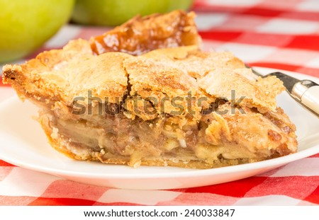 Slice of homemade apple pie on red plaid tablecloth with green apples in background. - stock photo