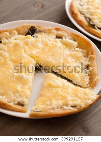 Slice of homemade pie with cheese in a white plate, closeup, selective focus, vertical - stock photo
