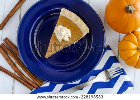 Slice of homemade pumpkin pie with whipped cream sitting on blue plate with small pumpkins and cinnamon sticks - stock photo