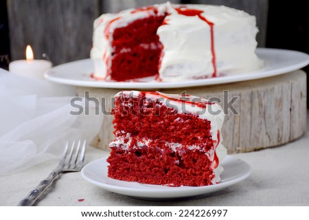 Slice of homemade red velvet cake on white plate, close up - stock photo