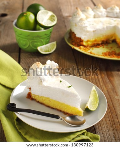 Slice of Key lime pie with fresh limes - stock photo