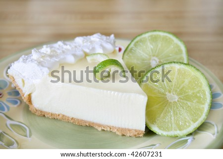 Slice of key lime pie with fresh limes and a garnish. - stock photo