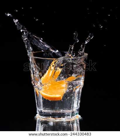 Slice of lemon splashing into a glass of water with a spray of water droplets in motion suspended in the air above the glass on a dark background. - stock photo