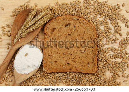 Slice of multi seeded brown bread on a wooden board with barley grains and ears of barley and flour in wooden spoons - stock photo