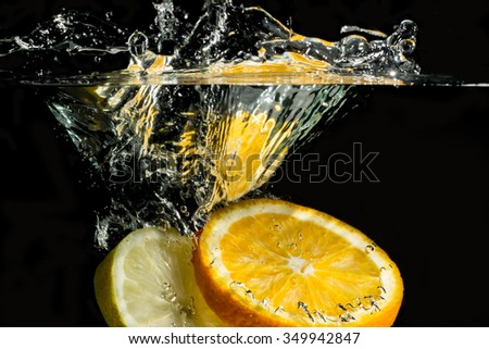 slice of orange falling into the water with a splash of water and air bubbles, on a black background - stock photo