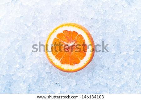 slice of orange fruit on a crashed ice - stock photo
