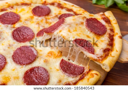 Slice of Pepperoni Pizza  being removed from whole pizza  - stock photo