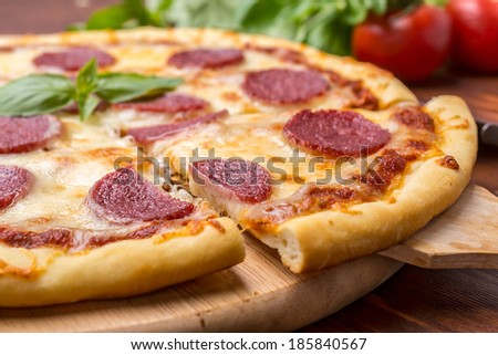Slice of Pepperoni Pizza  being removed from whole pizza with tomatoes in background - stock photo