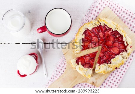Slice of pie with strawberry on napkins with pattern in peas, milk in jug and in red bowl, cream, on white wooden background. Top view - stock photo