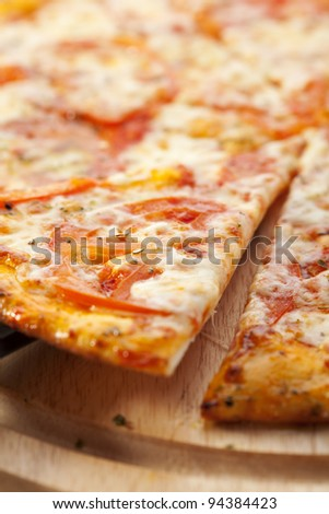 Slice of Pizza Margherita made with Tomatoes, Gauda Cheese and Mozzarella - stock photo