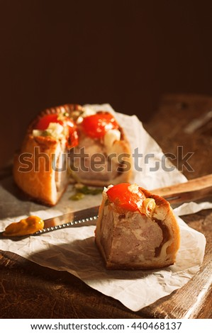 Slice of pork pie with knife loaded with mustard - stock photo