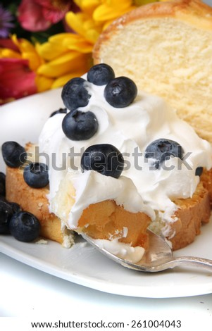 Slice of pound cake with whipped cream topped with blueberries and flowers in the background - stock photo