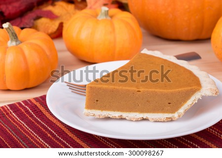 Slice of pumpkin pie with pumpkins in background - stock photo