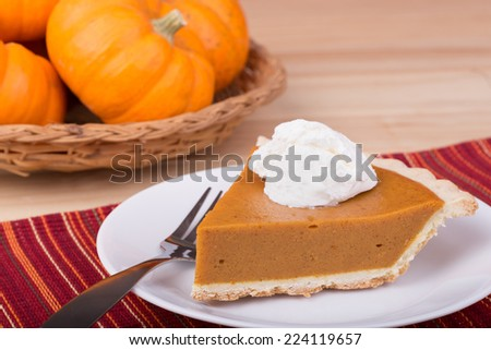 Slice of pumpkin pie with whipped cream and a basket of pumpkins in background - stock photo
