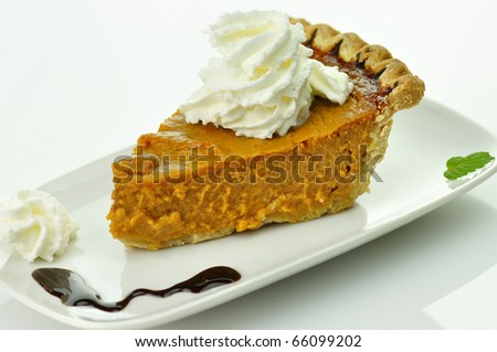 Slice of pumpkin pie with whipped cream on top - stock photo