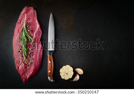 Slice of raw beef steak on dark background. Organic food. - stock photo