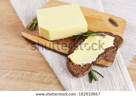 Slice of rye bread with butter on wooden cutting board  - stock photo