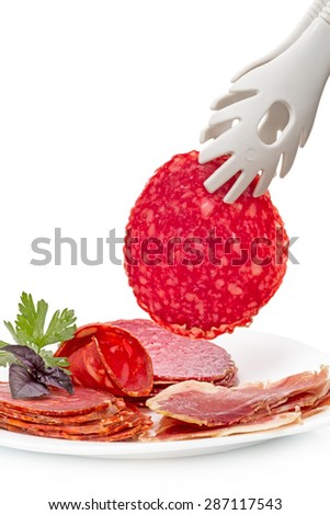 Slice of salami and meat products on a white plate - stock photo