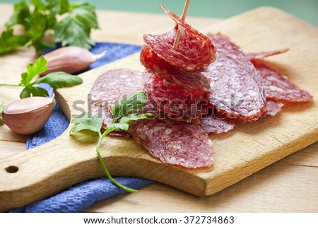 Slice of salami sausages on wooden board - stock photo