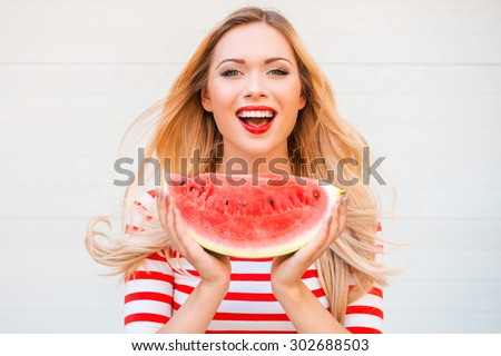Slice of summer goodness. Beautiful young woman holding slice of watermelon and smiling while standing outdoors - stock photo
