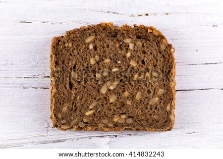 slice of sunflower bread on white wooden background, closeup, textured - stock photo