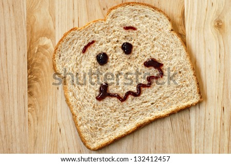 Slice of whole grain wheat bread with personality! - ('sweet' expression drawn on with grape jam) - on wooden cutting board. - stock photo
