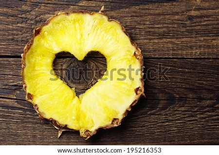 Slice pineapple with a cut in shape of hearts on vintage wooden background - stock photo