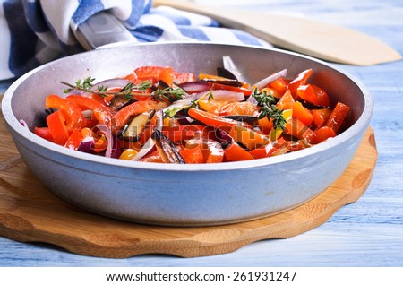 Sliced and cooked vegetables with thyme sprigs in the pan - stock photo