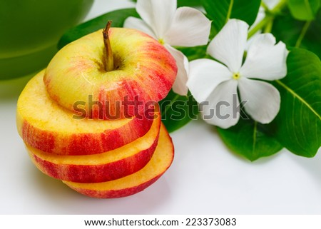 Sliced apple with vegetable juice and flower - stock photo