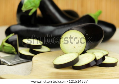 Sliced aubergine on a wooden cutting board - stock photo