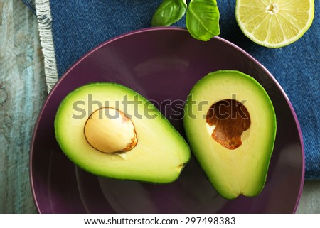 Sliced avocado and lemon lime on wooden background - stock photo