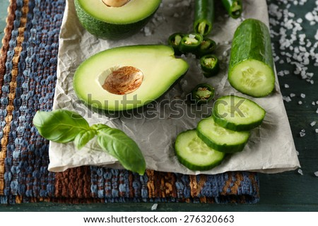 Sliced avocado, cucumber, pepper and lemon lime on wooden background - stock photo
