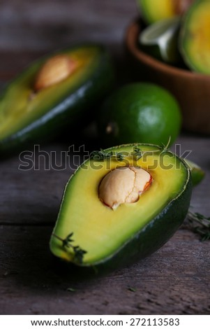 Sliced avocado with herb in bowl on wooden background - stock photo