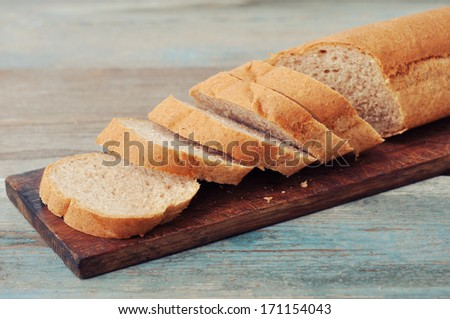 Sliced baguette on wooden cutting board closeup - stock photo